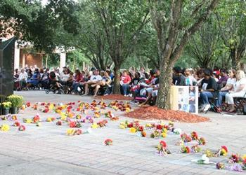 Dozens of families attended Monday night's 19th annual Unity Plaza Candlelight Vigil and Remembrance at Terry Parker High School. The flowers on the ground mark where new names of victims of violence are chiseled into bricks.