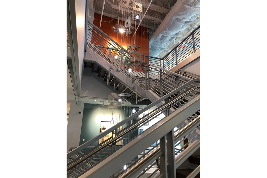 "A ""floating"" staircase connects the third through fifth floors, allowing employees access within the offices without having to use elevators or to move outside of the secured space."