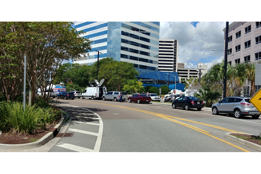 TV news vans line Independent Drive in front of the Jacksonville Landing on Monday.