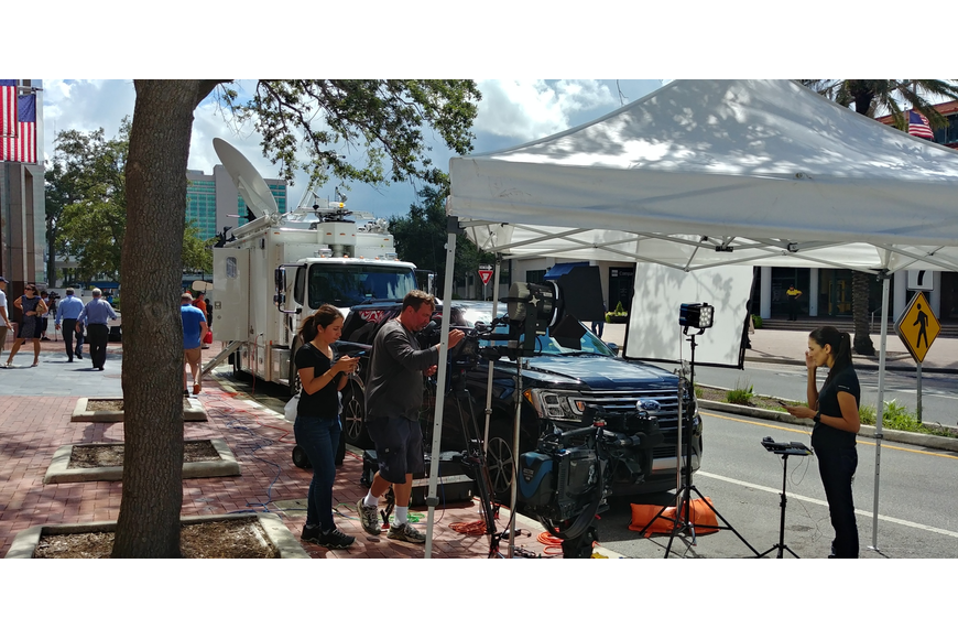 A television news crew works along Independent Drive on Monday in front of the Jacksonville Landing.