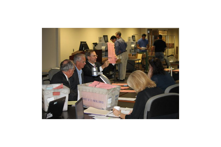 Supervisor of Elections Jerry Holland holds up a provisional ballot for a closer look Wednesday, a day after two local races were too close to name a winner. Tuesday's primary results must be finalized before the state can declare a recount for the St...