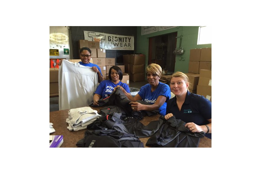 Volunteers from Florida Blue sort clothing at Dignity U Wear. The organization is kicking off its back-to-school campaign.