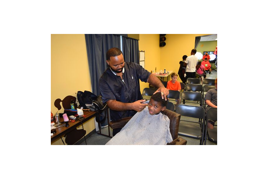 Steve Brightwell was one of four barbers who gave haircuts to children getting ready for school Aug. 13 at the Impact Church Arlington campus during the inaugural two-day Back-to-School Bash. The church adopted 13 public schools in the neighborhood an...