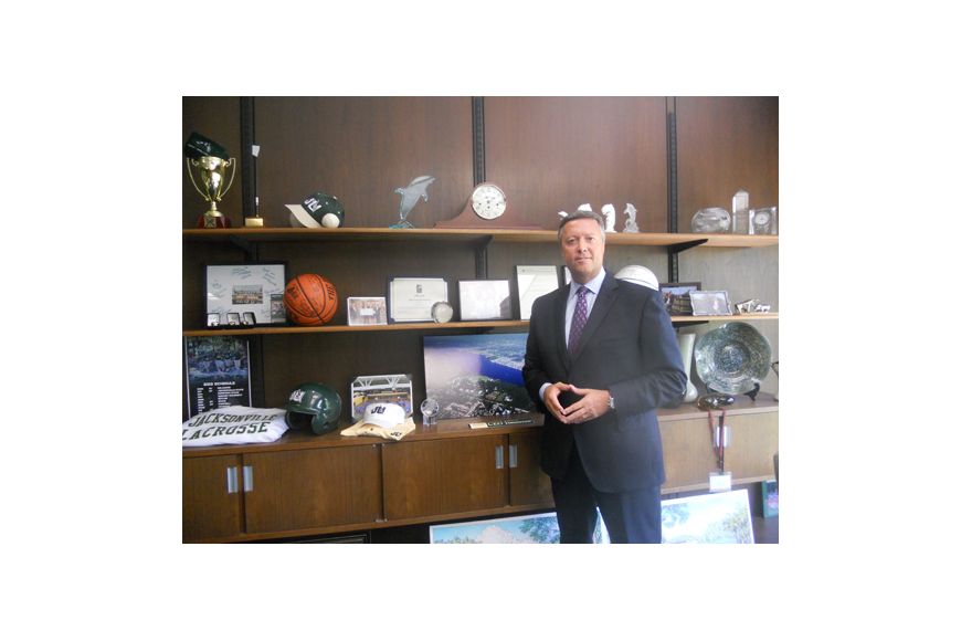Photo by Tracy Jones - Jacksonville University President Tim Cost tries to represent the many components of the college on his office shelves, including pieces from many of the sports teams.